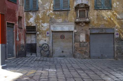 Graffiti image of a dead citizen in his square, from the old town centre of Genoa, Italy.
