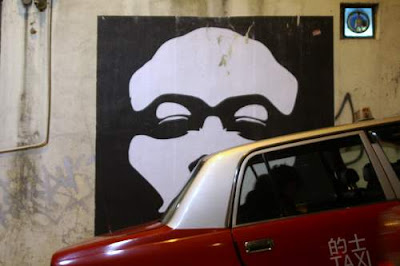 Graffiti image of a face, obscured by a taxi, found in Hong Kong (SOHO).