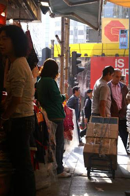 Image of a porter carrying goods by hand trolley and exiting an alley in Kowloon, Hong Kong.