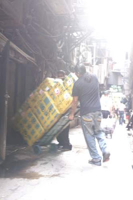 Image of a porter carrying cartons from Chungking Mansions to the quasi-legal moving trucks on the back street.