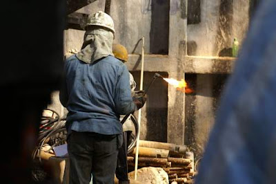 Image of a Hong Kong construction worker having just lit an oxy-acetylene torch.