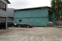Image of a carport and garage made of containers.
