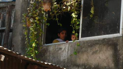 Image of a woman and child, peering out of their window, in India.