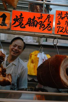 Image of Cantonese BBQ pork being sold from a small store in an alley, in Hong Kong.