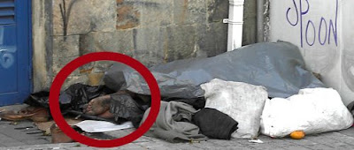 Dentro del círculo rojo se adivinan los pies de un hombre que duerme al abrigo de las miradas inquisidoras cubierto por unos plásticos. Bogotá, marzo 2008. Pero podría ser Barcelona