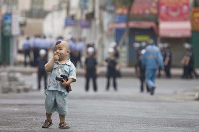 An+ethnic+Uighur+boy+holds+a+toy+gun+in+