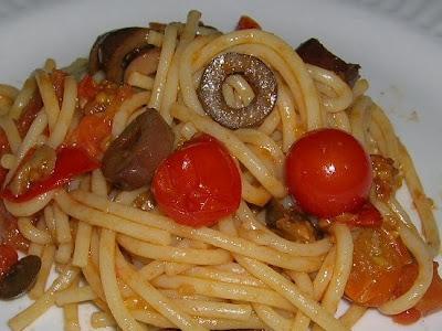 Pasta con tomates , anchoas y aceitunas.