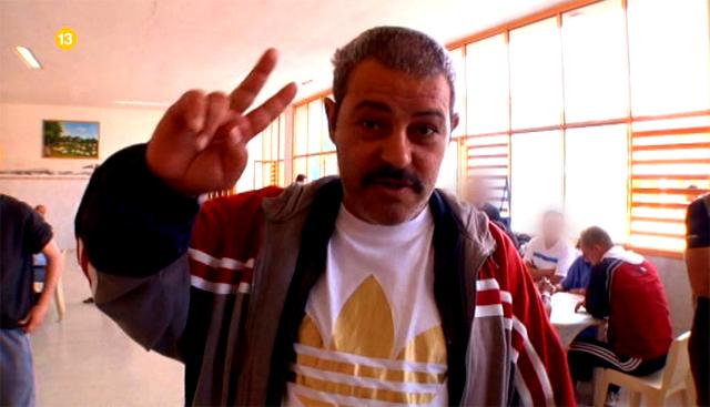 Un preso en la cárcel haciendo el gesto de la paz
