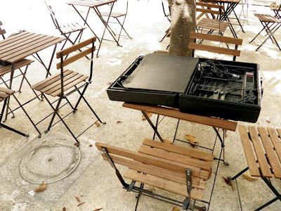Handlicher Koffer auf einem Tisch inmitten von Tischen und Stühlen