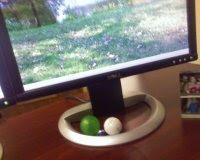 A green bouncy-ball, a golf ball, and a marble