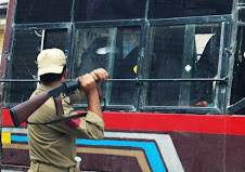 Brave Indian Policeman breaking window panes of a bus with Kashmiri women
