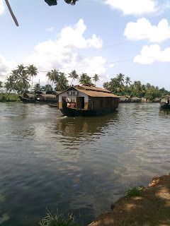cozy inner and outer view of a giant house boat with two floors- one conference area for around 200 peoples on the top and 6 air-conditioned   luxury bed rooms in the bottom at punnamada finishing point alappuzha backwaters kerala where the World famous Nehru Trophy Boat race happens once in a year