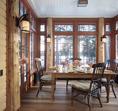 Dining room with windows on three sides, log columns, beadboard ceiling and country dining table and chairs by Peter Pennoyer