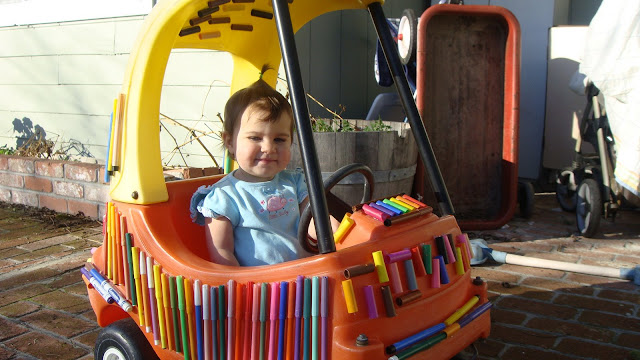 Girl in her toy pen car