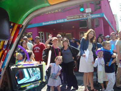 People in a parade waving at the Mercedes Pens