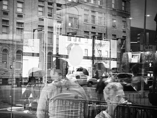 New York reflected in the window of Momofuku Ssäm Bar