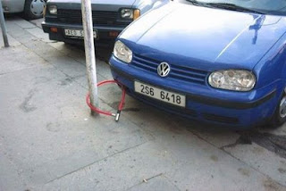 funny photo of volkswagen locked up to a pole with bike chain