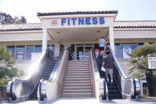 funny photo of fitness center that has escalators at entrance
