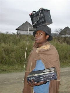 totally really funny photo of man carrying a stereo with a large battery on his head for power