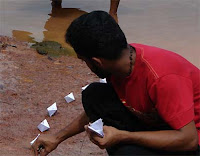 Student placing paper boats in a line at Sasthamkotta Lake, photo by V.Sasikumar