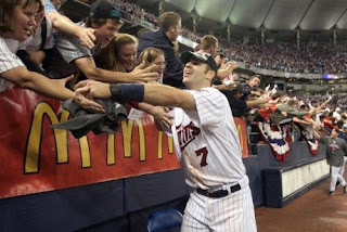 Joe Mauer high-fiving fans at a Twins Game