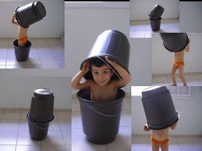 No centro, menininho sorridente surgindo de dentro de um balde e segurando outro sobre a cabeça. Em volta, imagens menores do mesmo menino em 5 diferentes momentos de brincadeira com os dois baldes.