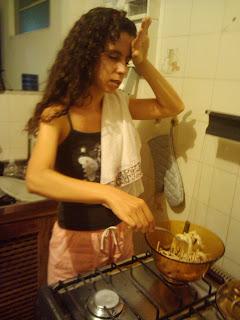 Sara, com cara sofrida, pano de prato no ombro, mão na testa, mexendo um macarrão no fogão.