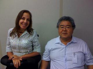 Mara sorrindo ao lado de Milton Oshiro,com  fortes traços orientais e cabelos grisalhos, ele veste uma camisa azul clara e óculos de aramação fina
