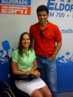 Mara Gabrilli,vestindo saia branca e camisa verde, ao lado de Raí,com polo vermelha e calça jeans. Os dois são fotografados dentro do estúdio do Derrubando Barreiras