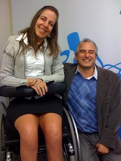 Mara,  de saia e blusa de lã, ao lado de Naziberto,de colete azul, blazer marron e calça cinza, sorrindo com a apresentadora