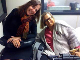 Mara sorrindo ao lado de Gilda, sentada em seu carrinho elétrico vestindo blusa rosa e casaco cinza e óculos de armação vermelha, ela sorri ao lado da apresentadora Mara Gabrilli