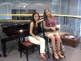 Sara Bentes, de calça branca, blusa preta e sapatos vermelhos ao lado de Mara Gabrilli. As duas estão sentadas em frente a um piano na Rádio Eldorado