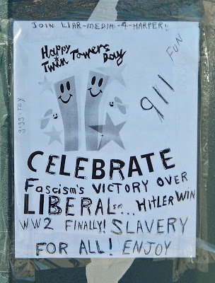 [Photo: poster reads: JOIN LIAR-MEDIA-4-HARPER! Happy Twin Towers Day 911 FUN CELEBRATE Fascism's VICTORY OVER LIBERALsm [sic]... HItLER WIN WW2 FINALLY! SLAVERY FOR ALL! ENJOY]