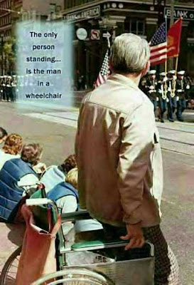 A handicapped veteran stands for the colors