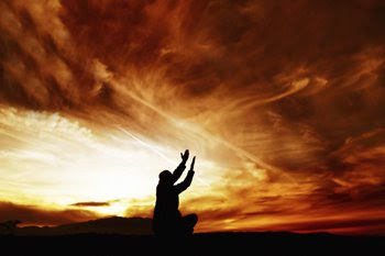 Sunset with a man praying with uplifted hands