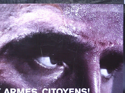 photo of a billbord displaying a pair of grim darj eyes and the words Armes Citoyens partially visible at the bottom