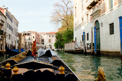 A Gondola navigates a Canal - Venice, Italy