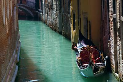 A Gondola parked along a canal - Venice, Italy
