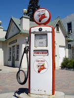 Photo of an old gas pump in front of a steep-roofed building.