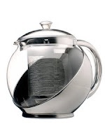 Photo of a metal and glass teapot.