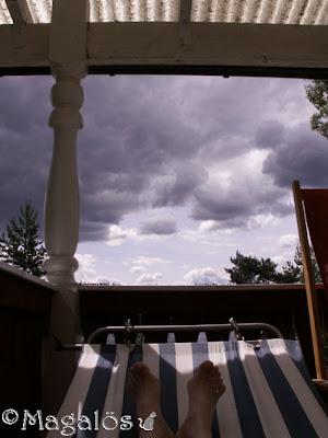 Mörka moln och bleka fötter i en hängmatta.