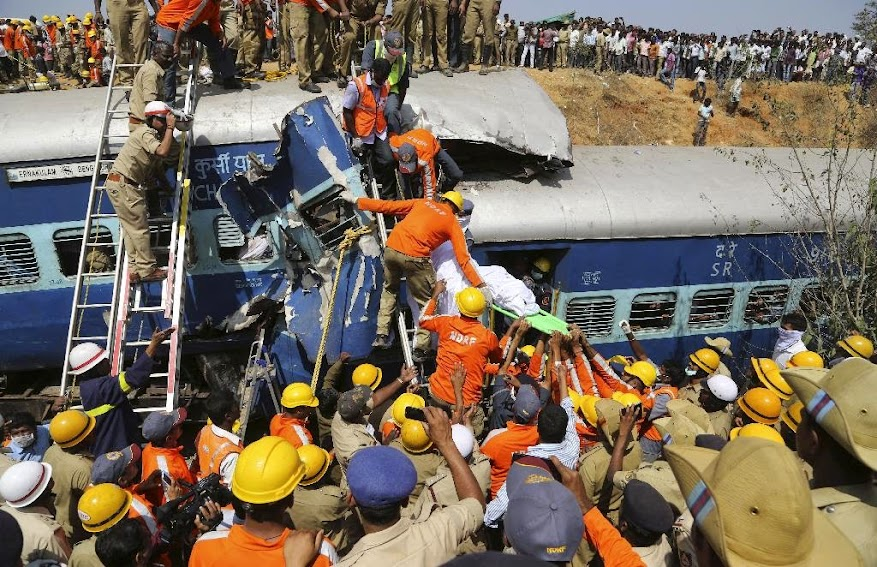Rescuers carry out the body of a passenger after pulling it out from a crumbled compartment of a derailed train near Anekal, 40 kilometers (25 miles) south of Bangalore, India, Friday, Feb. 13, 2015. The train derailed after hitting a boulder that had fallen on the track in southern India on Friday, killing more than 10 people, officials said.