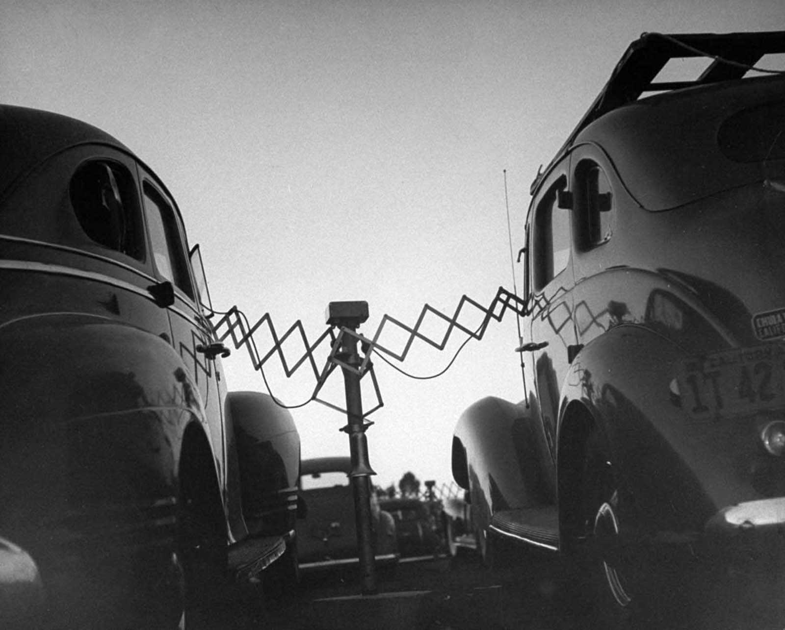 Cars parked at Rancho Drive-In Theater with the accordion-like fulcrum arms of movie speakers reaching into each driver's front window, which they will push back onto the central post when the movie is over.