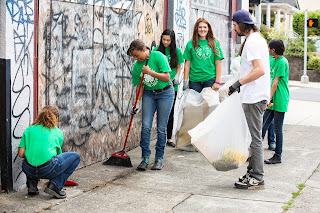 Five teenagers beautifying a city street with an adult volunteer