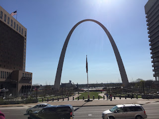 Photo the the St. Louis Arch framed by the buildings on either side, taken from the Old Courthouse.