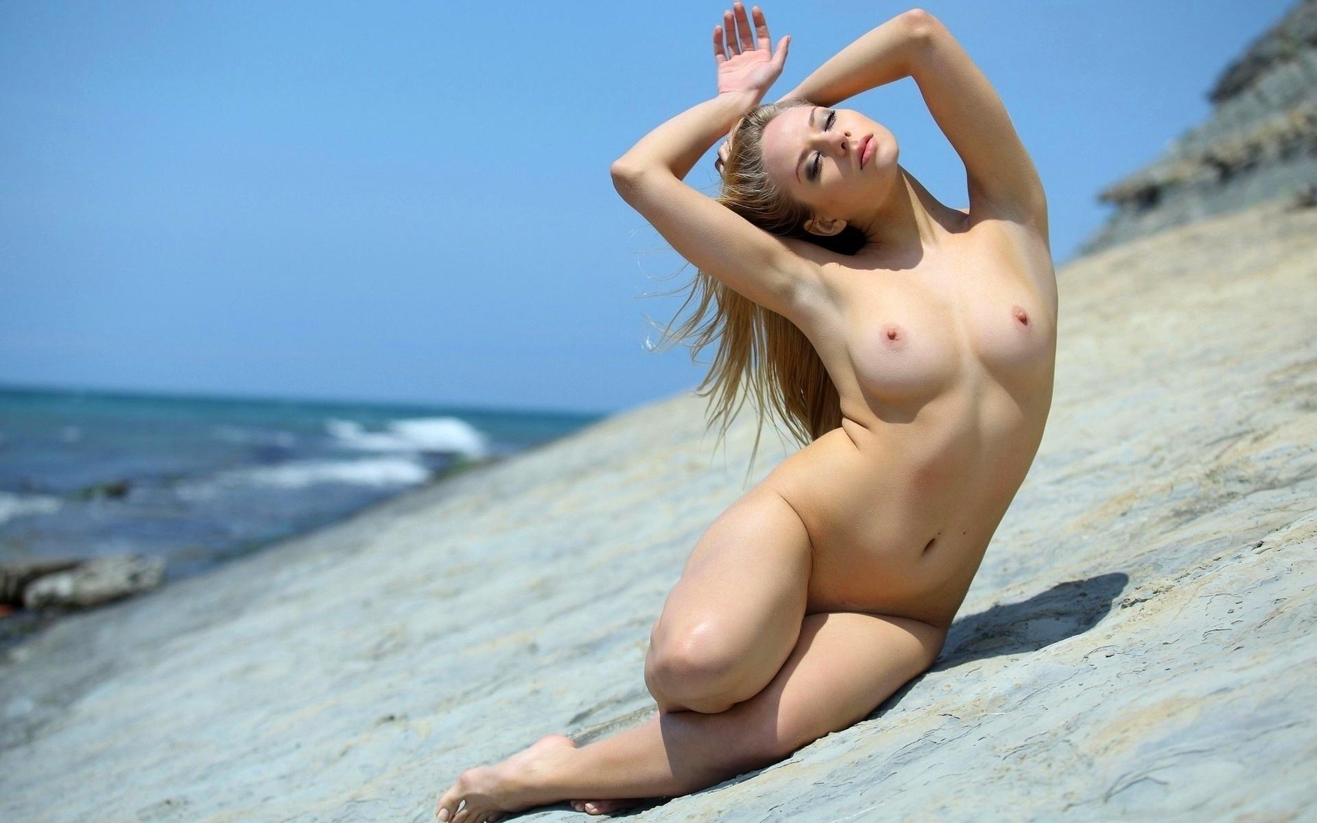 Белокурая стройная красавица разгуливает в бикини и голышом у океана