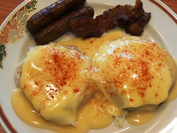 Eggs Benedict on a plate with sausage and baco