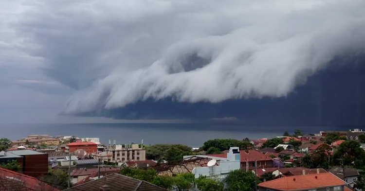 A massive cloud hovering over a sea.