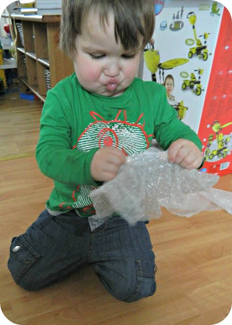 Small boy toddler popping bubble wrap