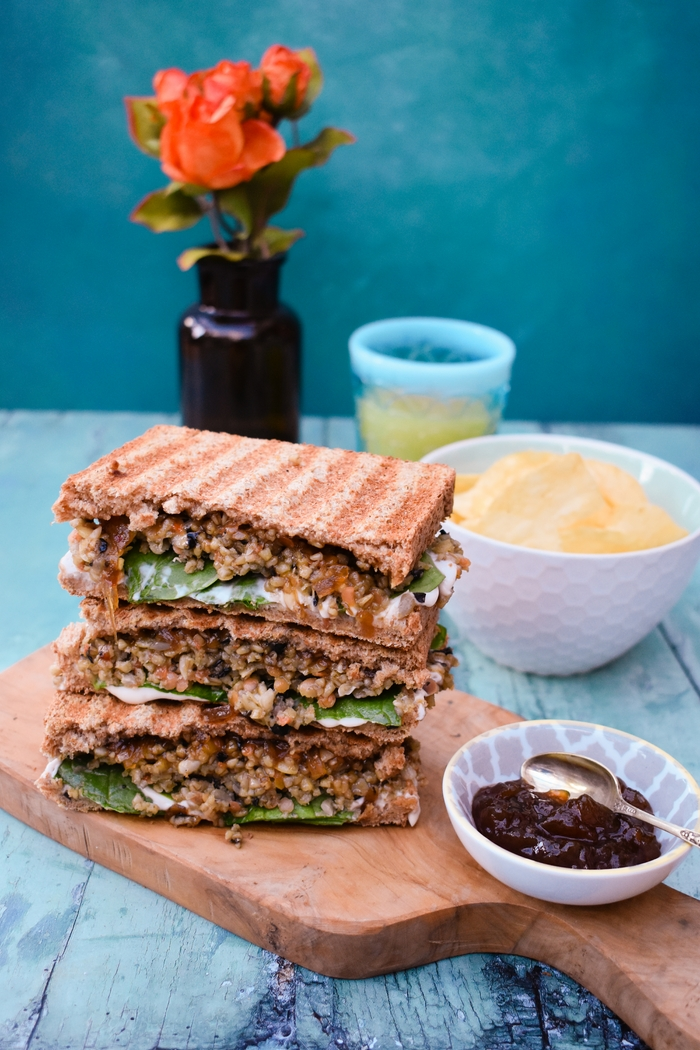 Veggie Haggis and Onion Chutney Toasties on a wooden board served with a bowl of pickle